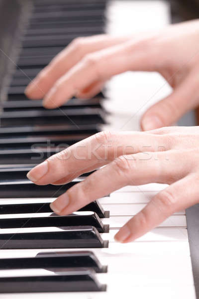 Woman\'s hands playing music on the piano