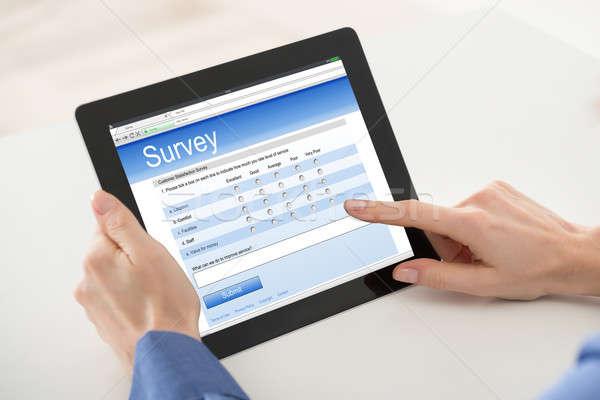 Close-up Of Woman Filling Online Survey Form On Digital Tablet