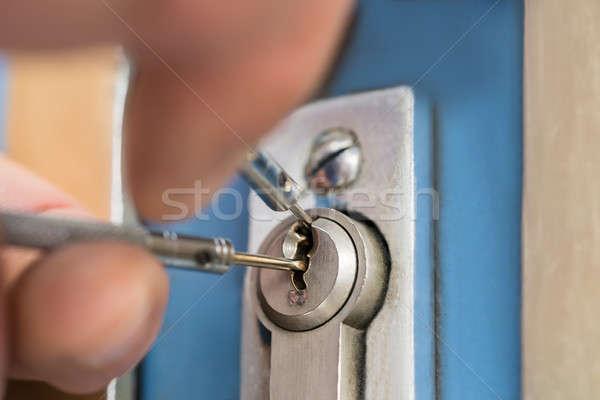 Close-up Of Lockpicker Hand Fixing Door Handle At Home