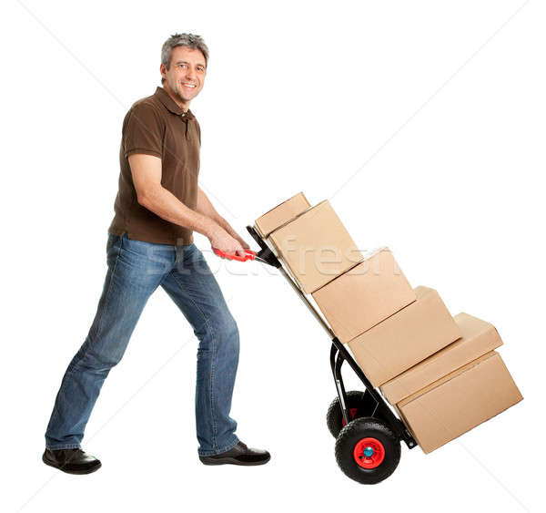 Stock photo: Delivery man pushing hand truck and stack of boxes