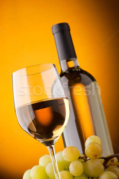 Stock photo: Bottom view of a glass of white wine bottle and grapes
