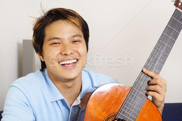 A handsome man holding a guitar
