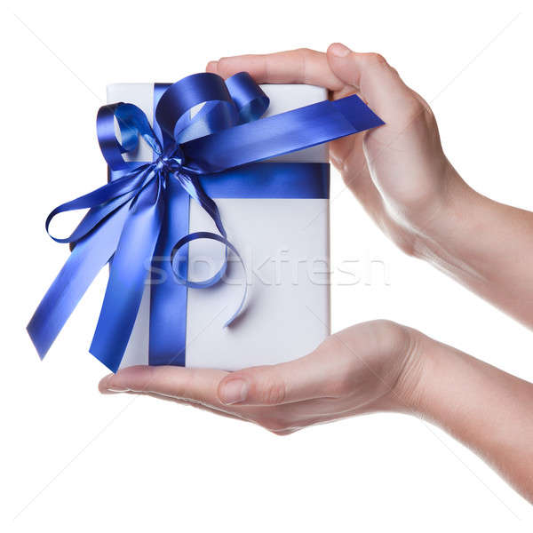 Stock photo: Hands holding gift in package with blue ribbon isolated on white