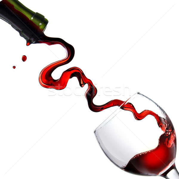 Stock photo: Pouring red wine in glass goblet isolated on white