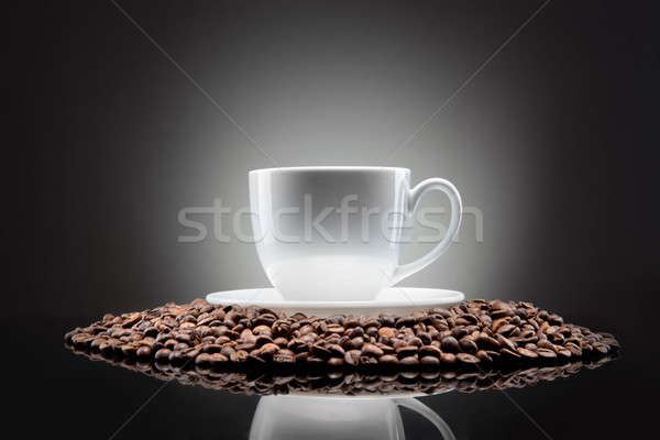 Stock photo: white cup with coffee beans on black