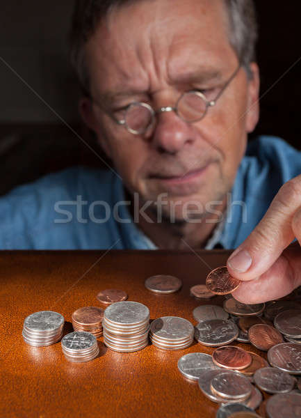 Stock photo: Senior man counting cash into piles