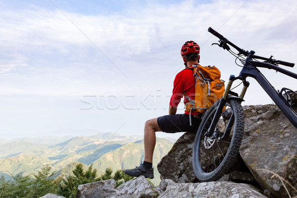Mountain biker looking at view on bike trail in autumn mountains. Rider cycling on single track. Sport fitness, motivation and inspiration in beautiful inspirational landscape.