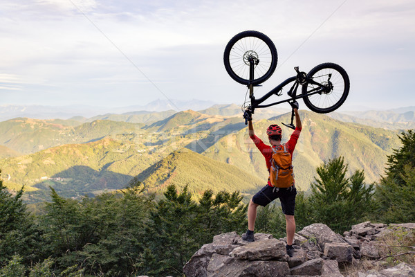 Mountain biker success, looking at view celebrating with bike up on trail in autumn mountains. Successful happy rider on rocks holding bicycle. Sport, adventure, motivation and inspiration.