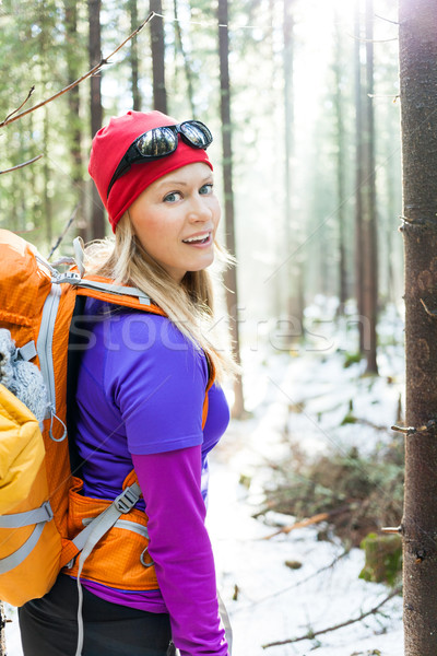 Woman hiking in white winter forest, backlight by morning sunlight rays, recreation and healthy lifestyle outdoors in nature. Beauty blond hiker backpacker looking at camera on sunrise.