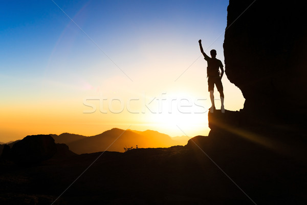 Man climbing hiking exploring silhouette in mountains, sunset and ocean. Male hiker with backpack on top of mountain looking at beautiful night landscape.