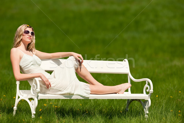 Stock photo: Spring - Young woman relaxing on bench in meadow
