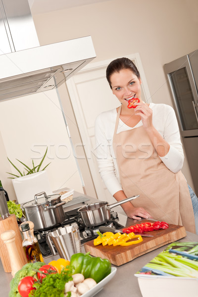 Stock photo: Smiling happy woman biting red pepper in the kitchen