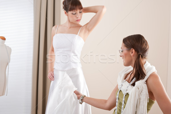 Stock photo: Fashion model fitting white wedding dress by designer