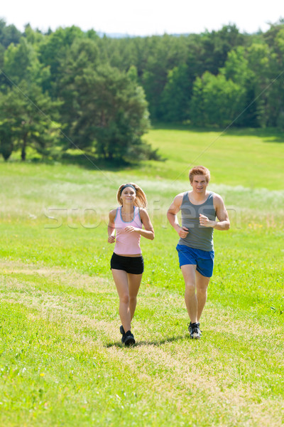 Stock photo: Sportive young couple jogging meadows sunny summer