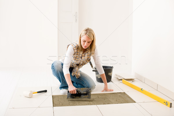 Stock photo: Home improvement, renovation - handywoman laying tile