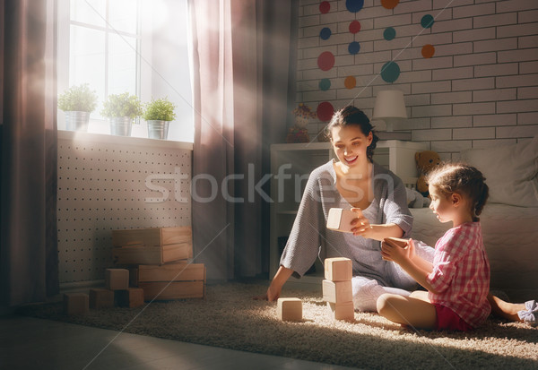 Happy loving family playing with blocks and having fun. Mother and her child daughter girl playing together.