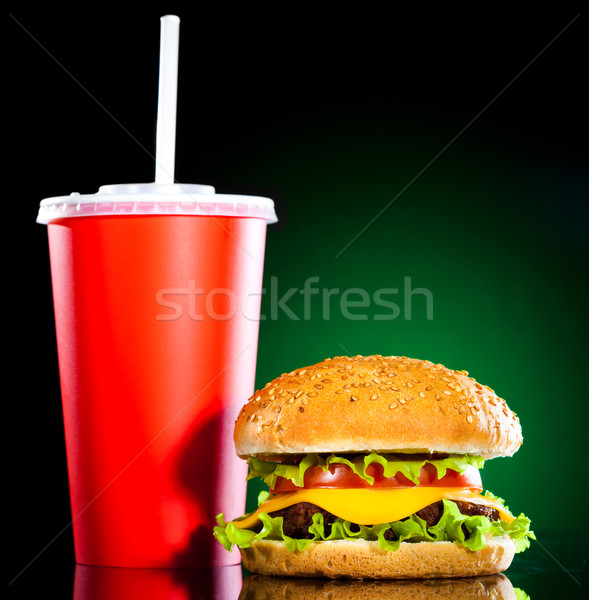 Stock photo: Tasty and appetizing hamburger on a darkly green