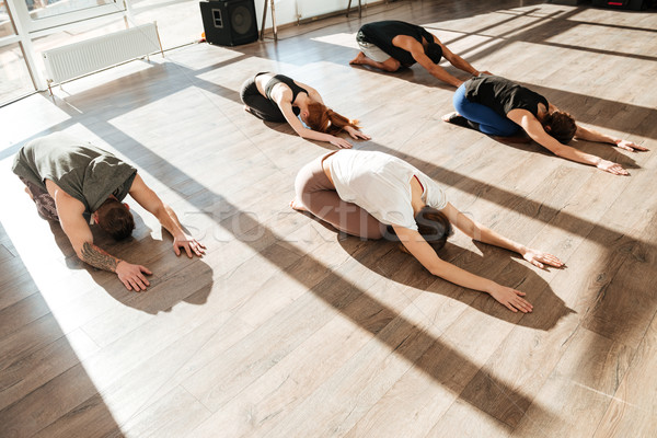 Stock photo: Group of relaxed young people doing yoga asana in studio