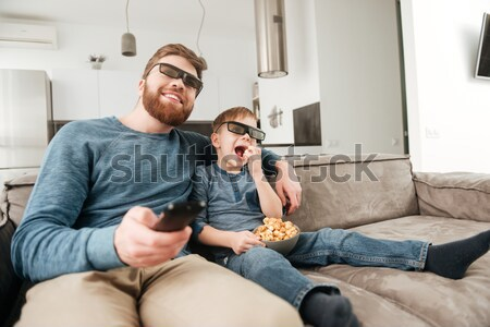 Stock photo: Little boy watching TV with 3d glasses and holding popcorn