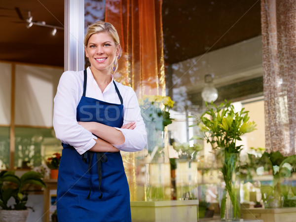 Stock photo: Young pretty woman working as florist in shop and smiling