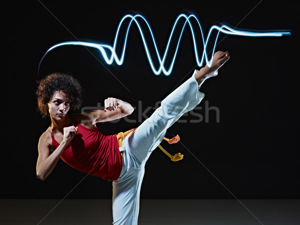 Stock photo: young adult latin american female doing capoeira side kick in ...
