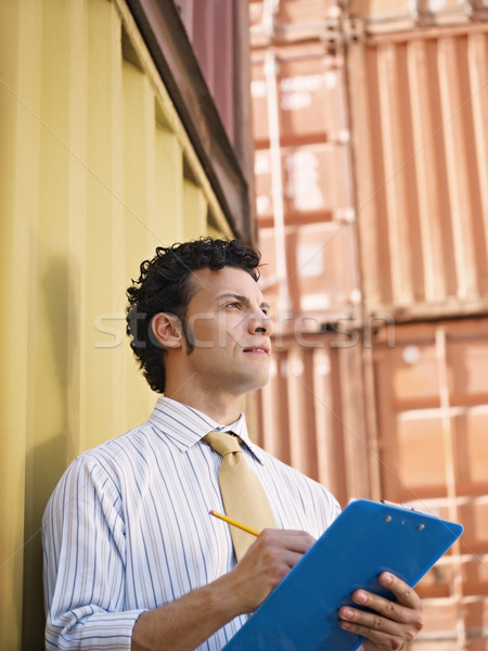 portrait of mid adult businessman leaning on cargo container and looking up. Vertical shape, side view, copy space