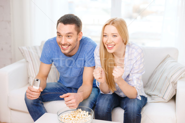 Stock photo: smiling couple with popcorn cheering sports team