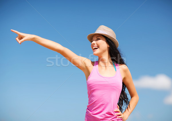 summer holidays and vacation - girl in hat showing direction on the beach