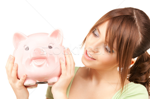 Stock photo: lovely teenage girl with piggy bank