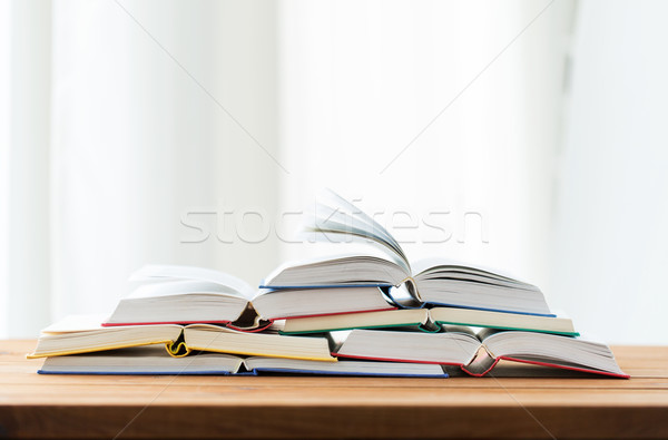 education, school, literature, reading and knowledge concept - close up of books on wooden table