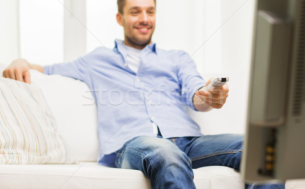 home, people, technology and entertainment concept - close up of man watching tv and changing channels with remote control at home