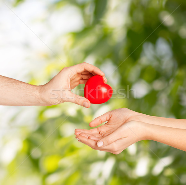 Stock photo: man hand giving red heart to woman