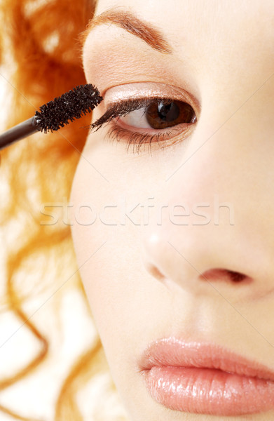 Stock photo: lovely redhead applying black mascara