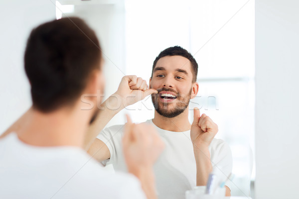 health care, dental hygiene, people and beauty concept - smiling young man with floss cleaning teeth and looking to mirror at home bathroom