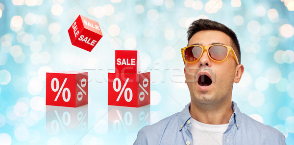 emotions, shopping, sale, discount and people concept - face of scared or surprised middle aged latin man in shirt and sunglasses over blue holidays lights and red percentage signs background