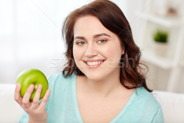 healthy eating, organic food, fruits, diet and people concept - happy young plus size woman eating green apple at home