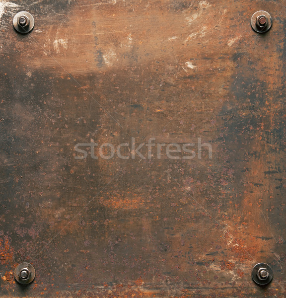 Rusty metal plate texture with bolts.