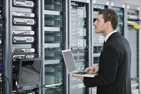 Stock photo: businessman with laptop in network server room