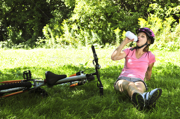 Stock photo: Teenage girl resting in a park with a bicycle drinking water