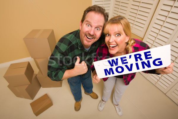Stock photo: Goofy Couple Holding We're Moving Sign Surrounded by Boxes