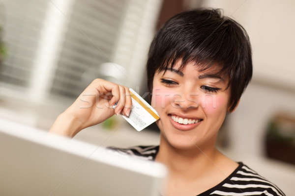 Stock photo: Smiling Multiethnic Woman Holding Credit Card Using Laptop