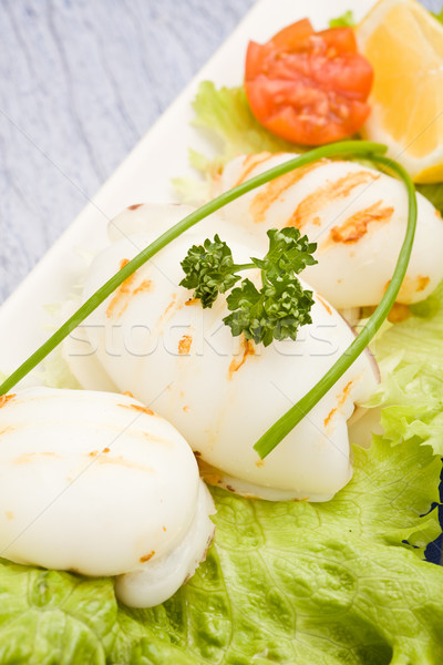 Stock photo: Squid with lettuce on blue glasstable