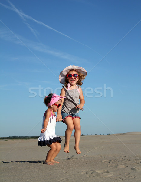 Stock photo: two happy little girl jumping
