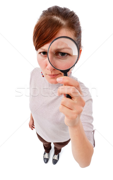 Stock photo: Serious woman as detective with magnifier
