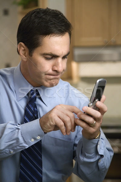 Stock photo: MId-adult Caucasian male pressing cell phone buttons while ...