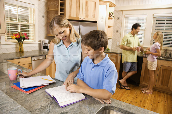 Stock photo: Family in kitchen doing homework and chatting.