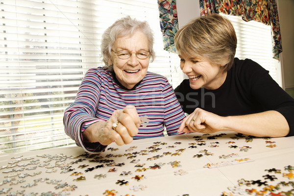 Stock photo: Elderly Woman and Younger Woman Doing Puzzle