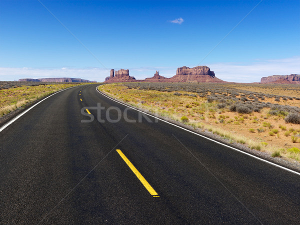 Remote desert road with mountain land formations.