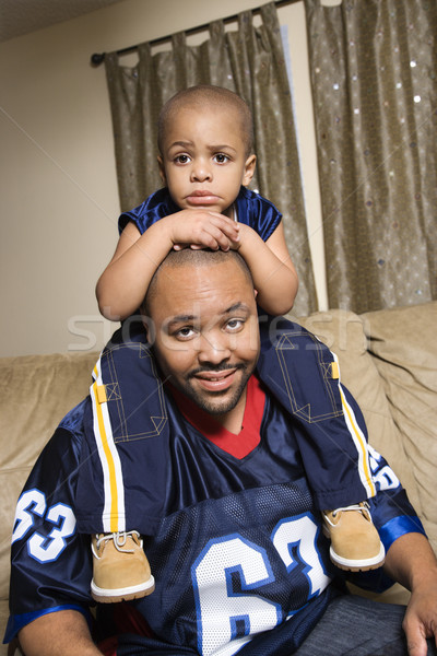 Portrait of African-American father with his son on his shoulders.