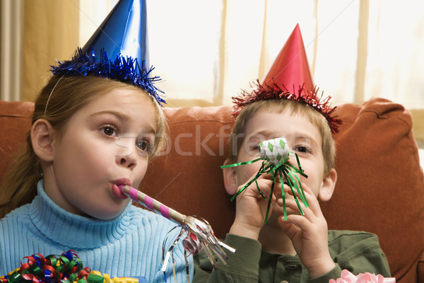 Stock photo: Children blowing noisemakers.